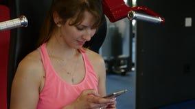 Glückliche sportliche Frau, die eine Mitteilung auf ihr Mobiltelefon an der Turnhalle schreibt stock footage