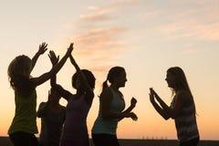 Glückliche sportliche Frauen, die gegen Sonnenuntergang zujubeln lizenzfreie stockbilder