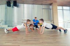Glückliche sportliche Kinder in der Turnhalle Stockfotografie