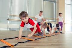 Glückliche sportliche Kinder in der Turnhalle Stockbilder