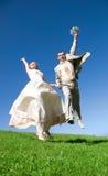 Glückliche springende Braut und Bräutigam auf dem Hügel Stockfotografie