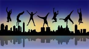 Glückliche springende Leute mit einem Nachtstadtschattenbild Lizenzfreies Stockfoto