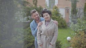 Glückliche Stellung der erwachsenen Frau des Porträts im Garten vor dem großen Haus, erwachsener Enkel, der sie, Setzen umarmt stock footage