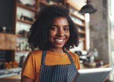 Glückliche Stellung der jungen Frau in ihrem Café lizenzfreie stockbilder