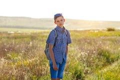 Glückliche Stellung des jungen Mannes mit Rucksackfreien am sonnigen Tag lizenzfreies stockfoto