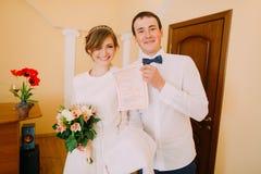 Glückliche stilvolle blonde Braut und hübscher Bräutigam, die Heiratsurkunde hält Stockfoto