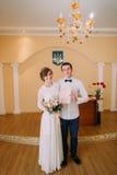 Glückliche stilvolle blonde Braut und hübscher Bräutigam, die Heiratsurkunde hält Stockbilder