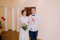 Glückliche stilvolle blonde Braut und hübscher Bräutigam, die Heiratsurkunde hält Lizenzfreie Stockbilder