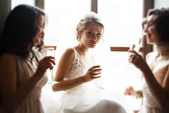 Glückliche stilvolle herrliche blonde Braut mit Brautjungfern auf dem BAC Stockbild