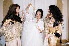 Glückliche stilvolle herrliche blonde Braut mit Brautjungfern auf der Rückseite Lizenzfreie Stockbilder