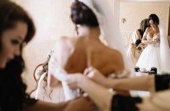 Glückliche stilvolle herrliche blonde Braut mit Brautjungfern auf der Rückseite Stockfotografie