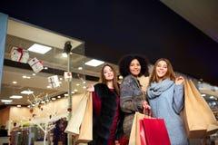 Glückliche stilvolle junge multiethnische Frauen mit Einkaufstaschen im Einkaufszentrum mit Papiertüten Kaukasisch und afroamerik lizenzfreie stockbilder