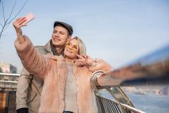 Glückliche stilvolle Liebhaber machen Foto draußen Stockfotos