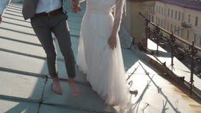 Glückliche stilvolle Paarbraut und -bräutigam, die auf das Dach geht stock video footage