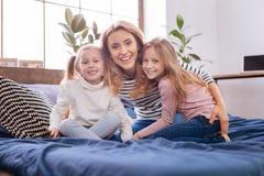 Glückliche streichelnde Mutter und ihre Töchter Stockbild