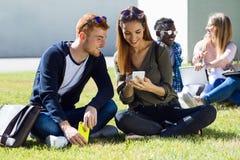 Glückliche Studenten, die draußen auf dem Campus an der Universität sitzen Lizenzfreie Stockfotografie