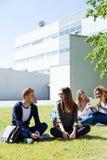 Glückliche Studenten, die draußen auf dem Campus an der Universität sitzen Stockbilder