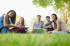 Glückliche Studenten, die draußen auf dem Campus sitzen Lizenzfreie Stockfotos