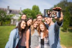 Glückliche Studenten, die draußen ein selfie auf dem Campus nehmen Stockfotografie