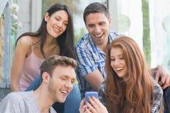 Glückliche Studenten, die draußen Smartphone auf dem Campus betrachten Lizenzfreie Stockbilder