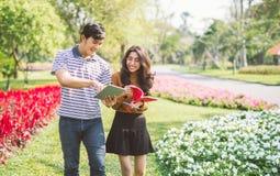 Glückliche Studenten, die in einem Campus am Park mit einem warmen Licht gehen und sich sprechen stockfotografie