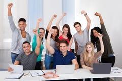 Glückliche Studenten, die Erfolg im Klassenzimmer feiern stockfoto
