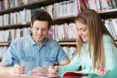 Glückliche Studenten, die zu den Notizbüchern in Bibliothek schreiben Stockfotografie