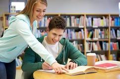 Glückliche Studenten, die zu den Prüfungen in der Bibliothek sich vorbereiten stockfoto