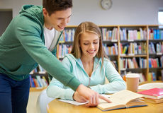 Glückliche Studenten, die zur Prüfung in der Schulbibliothek sich vorbereiten stockfotos
