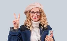 Glückliche Studentenfrau ist lächelnd zeigend und Friedenszeichen stockbilder