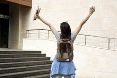 Glückliche Studentin im College mit den Armen angehoben in die Luft lizenzfreies stockbild