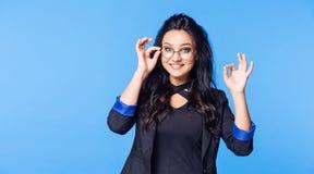 Glückliche Studentin mit Gläsern und eine schwarze Jacke, die Daumen zeigt, up O.K. stockbild