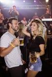 Glückliche tanzende Freunde beim Halten von Bierkrügen am Nachtklub Lizenzfreies Stockbild