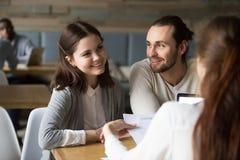 Glückliche tausendjährige Paare, die planen, Hypothekenvertrag an mir zu unterzeichnen lizenzfreies stockfoto