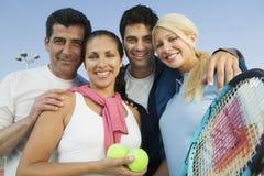 Glückliche Tennis-Spieler mit Schlägern und Bälle gegen Himmel Lizenzfreies Stockbild