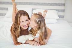 Glückliche Tochter, die Mutter beim Stillstehen auf Bett küsst lizenzfreies stockbild