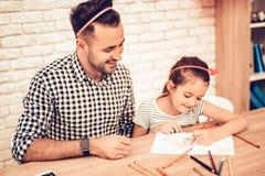 Glückliche Tochter mit Vater Draw Picture auf Tabelle stockfotografie
