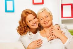 Glückliche Tochter und eldery Mutter umarmen mit smils Stockbilder