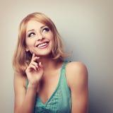 Glückliche toothy lächelnde blonde Frau, die oben denkt und schaut getont Lizenzfreies Stockfoto
