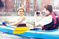 Glückliche Touristen, die Fotos in einem Kanu machen Stockfotografie