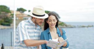 Glückliche Touristen, die Karte auf dem Strand im Urlaub überprüfend sprechen stock video