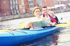 Glückliche Touristen mit einer Karte in einem Kanu Lizenzfreies Stockfoto