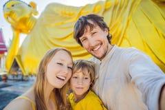 Glückliche Touristen Mutter, Vater und Sohn auf dem Hintergrund, der Buddha-Statue ofLying ist stockfoto