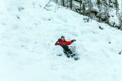 Glückliche touristische Antriebe in der schneebedeckten Steigung lizenzfreie stockfotos