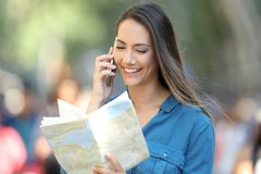 Glückliche touristische bittene Informationen über Telefon lizenzfreie stockbilder