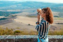 Glückliche touristische Frau, die Fotos mit Retro- Fotokamera macht stockfotografie