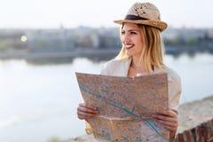 Glückliche touristische Frau im Urlaub mit Kartenbesuchsstadt lizenzfreie stockbilder