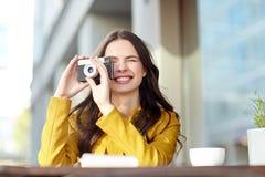 Glückliche touristische Frau mit Kamera am Stadtcafé Lizenzfreie Stockbilder
