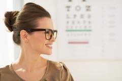 Glückliche tragende Brillen der jungen Frau vor Snellen-Diagramm lizenzfreie stockfotografie
