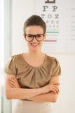 Glückliche tragende Brillen der jungen Frau vor Snellen-Diagramm lizenzfreies stockbild